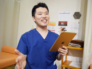 ipadを持っている柔道整復師の写真